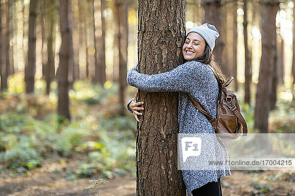 Happy female hiker embracing tree while hiking in Cannock Chase woodland during winter