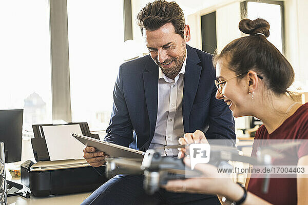 Business people using digital tablet while working with quadcopter at office