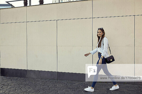 Businesswoman with purse walking against wall on footpath