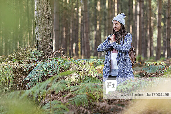 Female hiker doing yoga while standing in Cannock Chase woodland