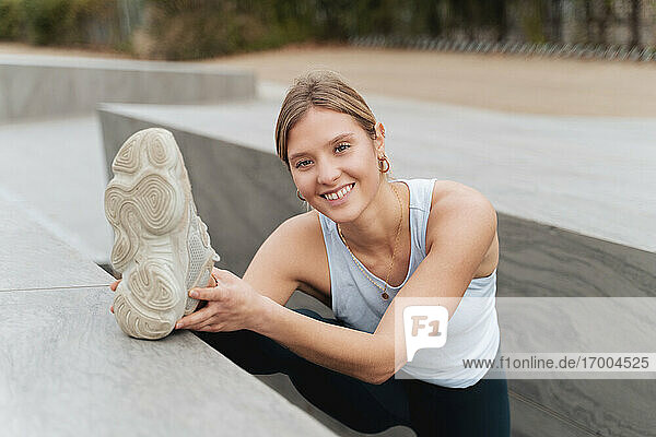 Smiling sportswoman exercising while stretching leg on retaining wall