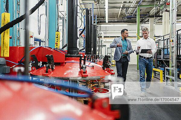 Geschäftsleute diskutieren beim Gehen in einer Fabrik