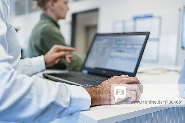 Geschäftsmann mit Laptop bei der Arbeit mit einem Kollegen im Büro