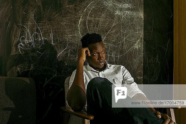 Nachdenklicher Geschäftsmann  der auf einem Stuhl vor einer bekritzelten Wand sitzt Nachdenklicher Geschäftsmann, der auf einem Stuhl vor einer bekritzelten Wand sitzt