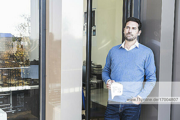 Businessman holding coffee cup while leaning on wall with hand in pocket at office entrance