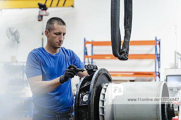 Männlicher Techniker  der eine Maschine repariert  während er in einer beleuchteten Fabrik steht