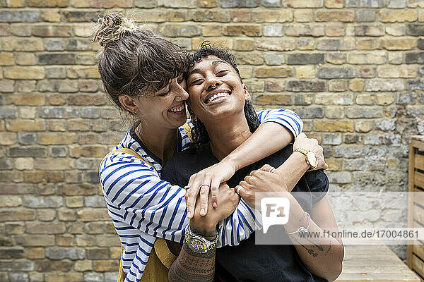 Happy woman embracing girlfriend while standing at back yard