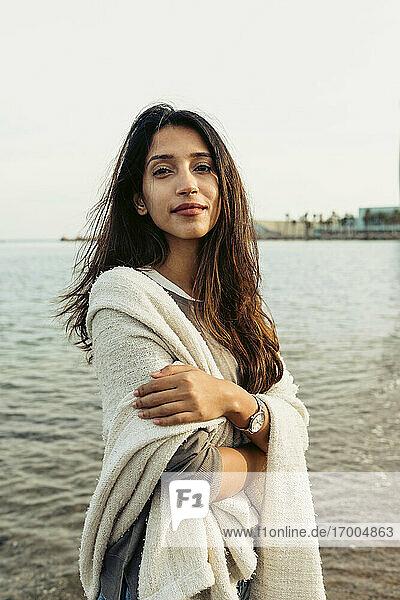 Schöne Frau mit verschränkten Armen am Strand stehend Schöne Frau mit verschränkten Armen am Strand stehend