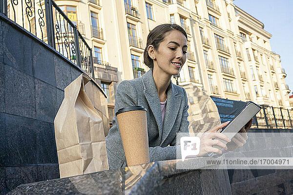 Unternehmerin  die ein digitales Tablet benutzt  während sie sich auf ein Geländer in der Stadt im Herbst stützt Unternehmerin, die ein digitales Tablet benutzt, während sie sich auf ein Geländer in der Stadt im Herbst stützt