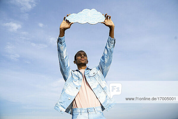 Man holding cloud cut out while standing against sky