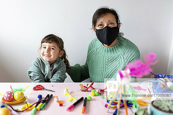 Grandmother wearing protective face mask sitting with granddaughter against wall