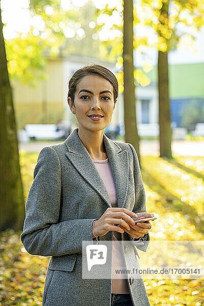 Schöne Geschäftsfrau hält Smartphone  während sie im Herbst im Park steht Schöne Geschäftsfrau hält Smartphone, während sie im Herbst im Park steht