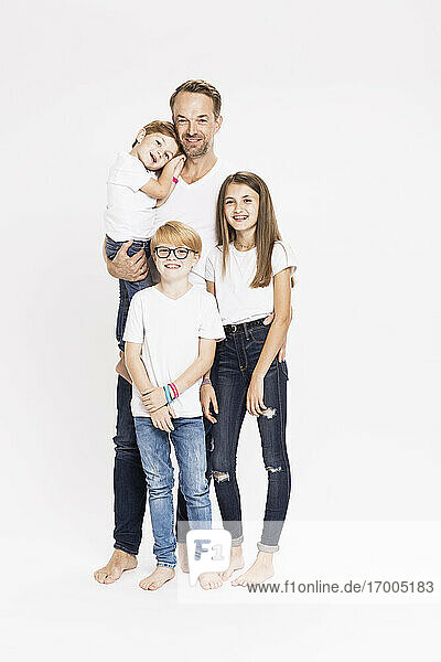 Happy mature man with children against white background