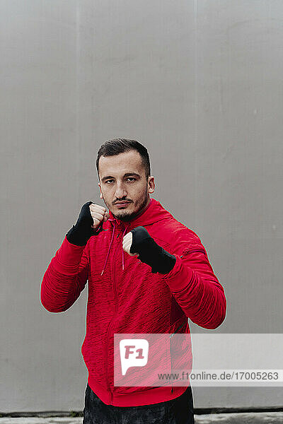 Confident sportsman with bandaged hand boxing while standing against wall