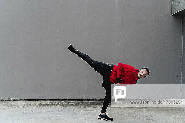 Sportsman practicing kickboxing while standing against wall