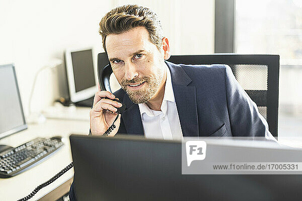 Businessman smiling while talking on telephone while sitting at office