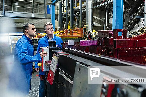 Ältere männliche Ingenieure  die in der Industrie stehend Produktionsanlagen prüfen