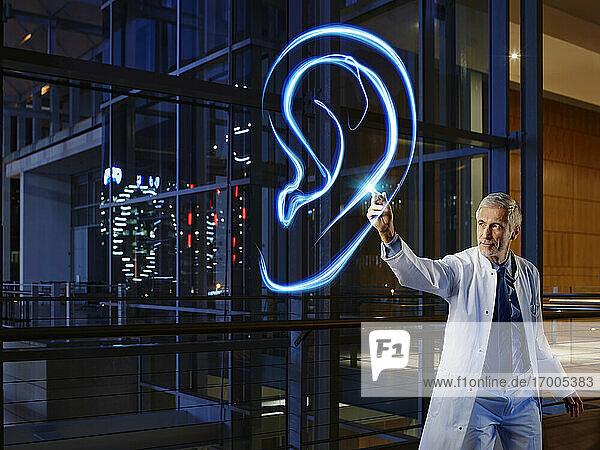 Male otolaryngologist examining ear in laboratory at hospital