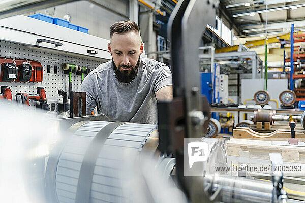 Mittlerer erwachsener männlicher Ingenieur  der ein Stahlmaschinenteil in der Beleuchtungsindustrie analysiert