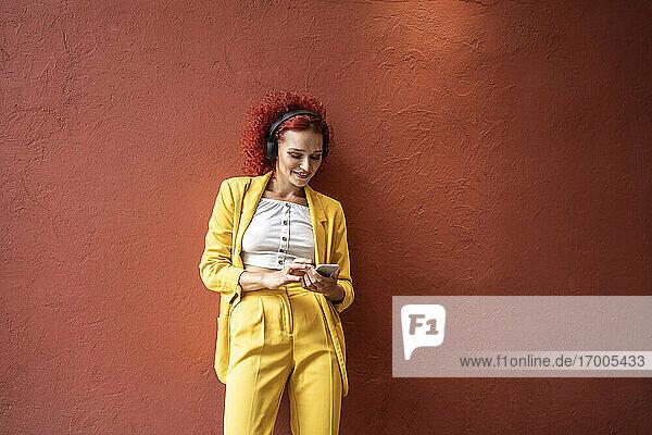 Junge Frau in gelbem Anzug lehnt an einer roten Wand  trägt Kopfhörer und benutzt ein Smartphone Junge Frau in gelbem Anzug lehnt an einer roten Wand, trägt Kopfhörer und benutzt ein Smartphone