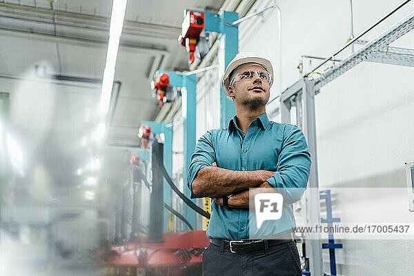 Male technician with arms crossed day dreaming while standing in factory