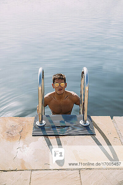 Portrait of young man wearing sunglasses getting out of the water