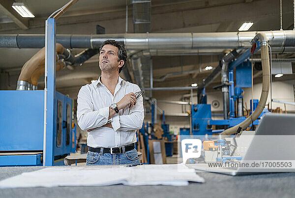 Porträt eines Schreiners  der Dokumente in einer Produktionshalle prüft