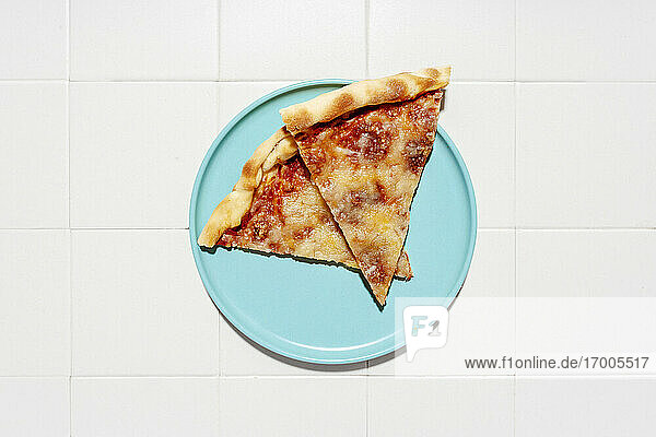 Two slices of pizzaMargheritaon blue plate