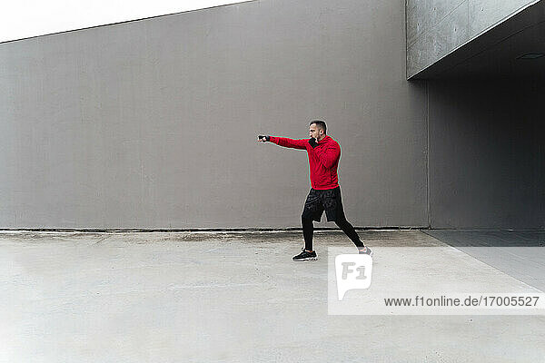 Male athlete boxing while standing against wall