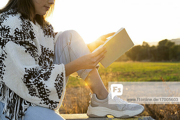 Young woman reading book while sitting on retaining wall during sunset