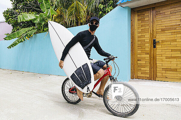 Man wearing protective face mask carrying surfboard while riding bicycle on footpath at Huraa Island  Maldives