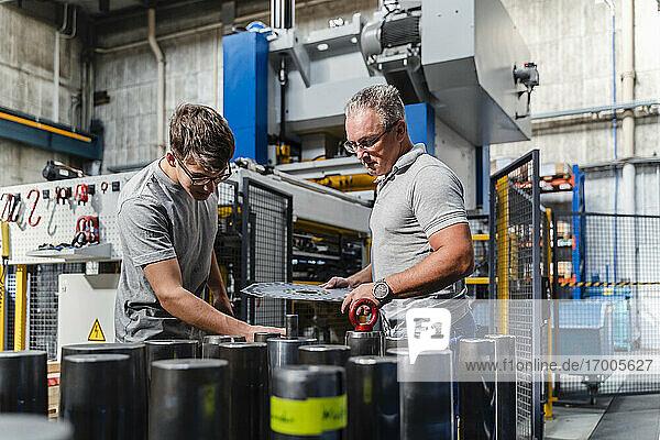 Männlicher Ingenieur  der ein Produkt mit einem älteren Techniker aus der Beleuchtungsindustrie untersucht