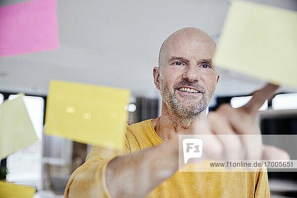 Mature man reading adhesive note