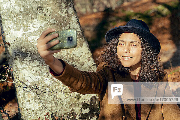 Woman smiling while taking selfie through mobile phone in forest