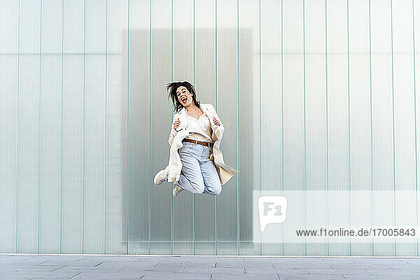 Cheerful Female entrepreneur jumping in mid-air against glass wall