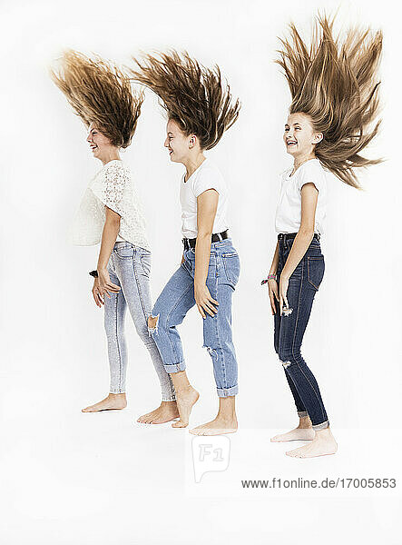 Playful sisters tossing hair against white background