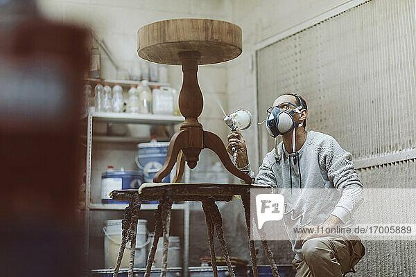Schreiner mit Gesichtsschutzmaske beim Lackieren des Tisches in der Werkstatt Schreiner mit Gesichtsschutzmaske beim Lackieren des Tisches in der Werkstatt