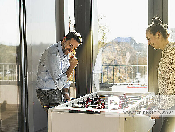 Smiling man showing winning gesture while playing Foosball with colleague at office