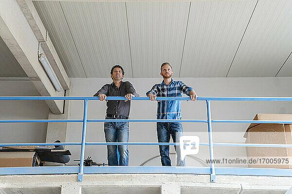 Zwei Zimmerleute im Gespräch vor einem Geländer in einer Produktionshalle