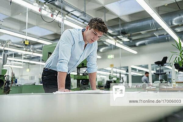 Geschäftsmann  der eine Blaupause am Schreibtisch in der Industrie prüft