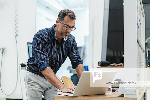 Male entrepreneur using laptop while standing in industry