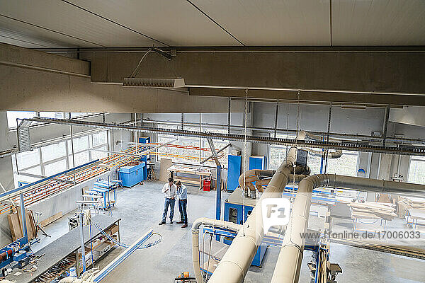 Two carpenters standing and talking in production hall