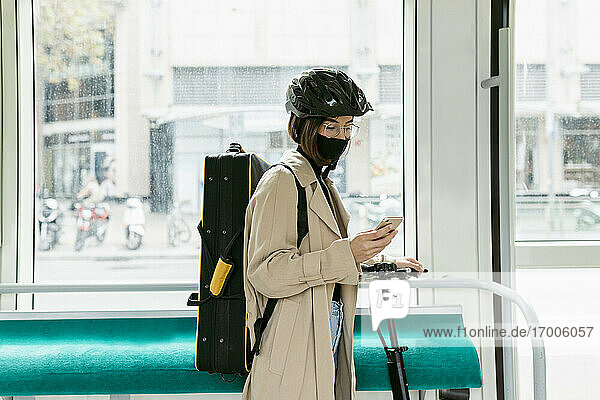 Frau mit Instrumententasche und Roller  die in der Straßenbahn steht und ein Mobiltelefon benutzt Frau mit Instrumententasche und Roller, die in der Straßenbahn steht und ein Mobiltelefon benutzt