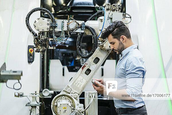 Männlicher Unternehmer  der ein Maschinenteil untersucht  während er an einem Roboterarm in der Industrie steht