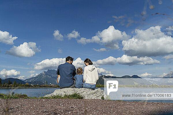 Familie mit kleiner Tochter sitzt gemeinsam auf einem Felsen am Seeufer