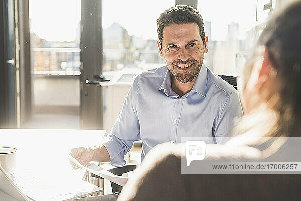 Smiling businessman working with colleague while sitting at office