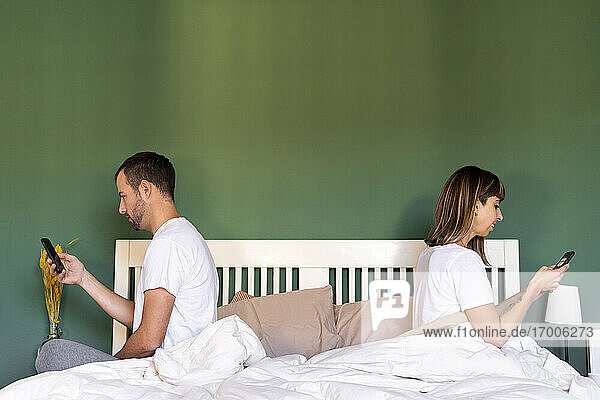 Mid adult couple using mobile phone while sitting on bed at home