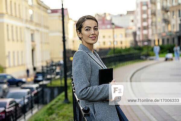 Smiling female entrepreneur holding diary while leaning on railing in city