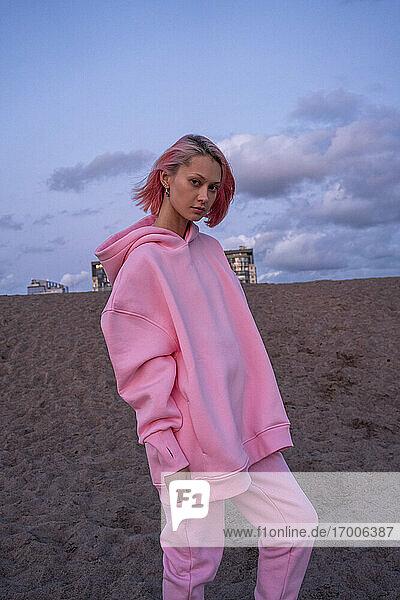 Porträt einer jungen Frau mit rosa Haaren und rosa Kapuzenshirt am Strand bei Sonnenuntergang Porträt einer jungen Frau mit rosa Haaren und rosa Kapuzenshirt am Strand bei Sonnenuntergang