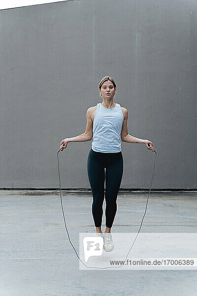 Young woman skipping rope while standing against wall
